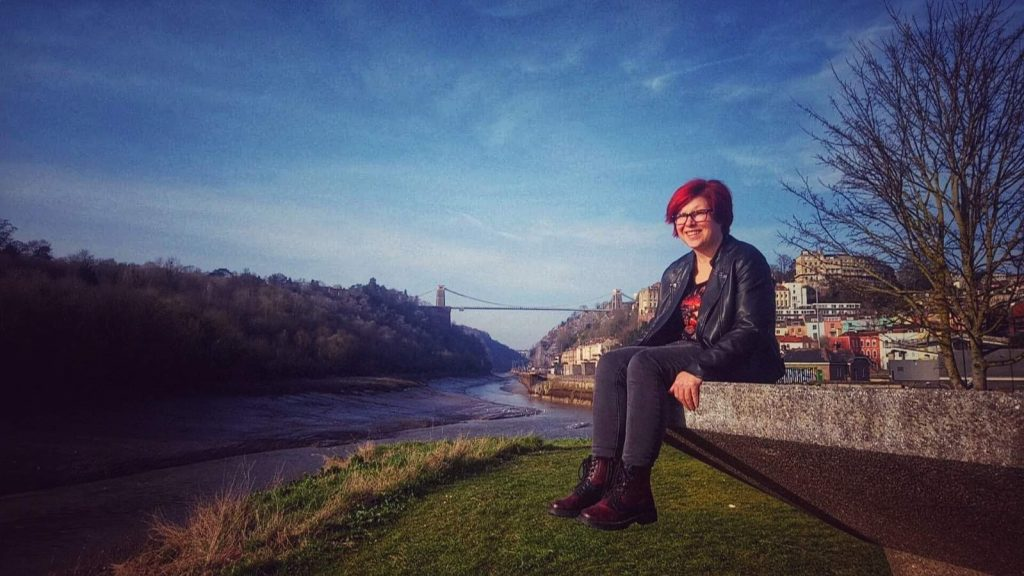Image of a woman sitting on concrete overlooking River Avon with Suspension Bridge in the distance.